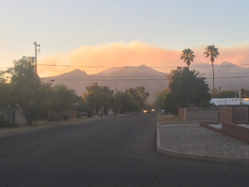 [Orange smoke over Catalina Mountains at sunset]