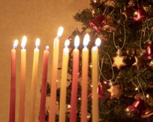 Menorah in front of Christmas tree